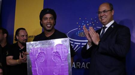 Brazil's former soccer player Ronaldinho shows his footprints, next to the Rio de Janeiro Governor Wilson Witzel (R), to be included in the Maracana's hall of fame, in Rio de Janeiro, Brazil
