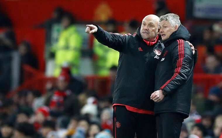 Manchester United coach Mike Phelan and interim manager Ole Gunnar Solskjaer, right, gesture on the touchline during the match against Burnley, during their English Premier League soccer match at Old Trafford in Manchester, England