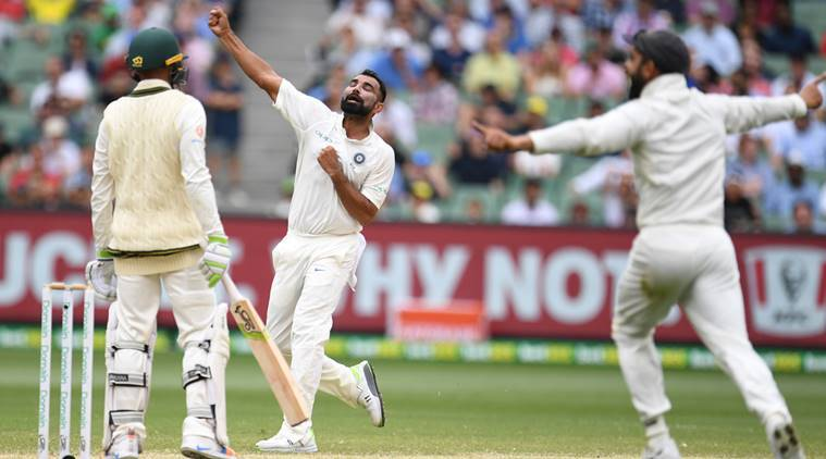 India's Mohammed Shami (C) reacts after dismissing Australia's Usman Khawaja (L) on day four of the third test match between Australia and India at the MCG in Melbourne, Australia