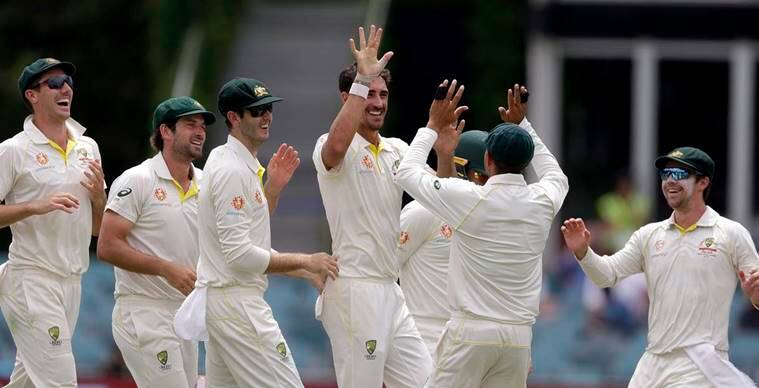 Australia's Mitchell Starc, center, celebrates with teammates after taking the wicket of Sri Lanka's Kusal Perera on day 4 of their cricket test match in Canberra