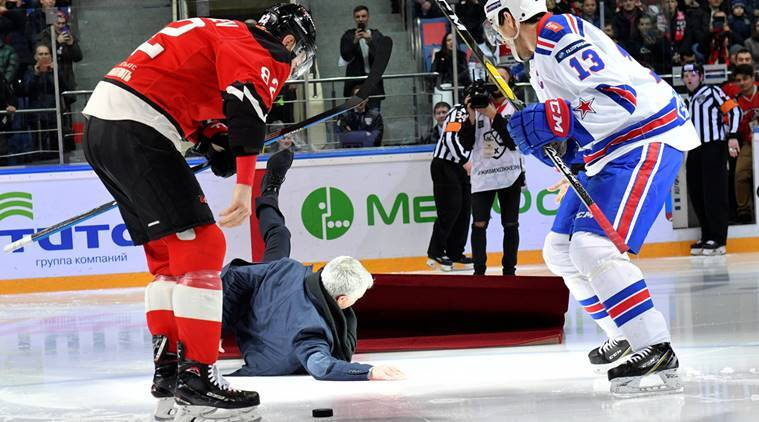 Jose Mourinho falls down, as ice hockey players Evgeny Medvedev and Pavel Datsyuk stand nearby, during a ceremony opening a game of Russia's Kontinental Hockey League (KHL) between Avangard Omsk and SKA Saint Petersburg in the city of Balashikha near Moscow, Russia
