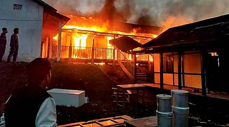 A building set on fire after a mob went on a rampage during a protest against the move to grant permanent resident certificates to six communities living in the state on Sunday. (PTI)