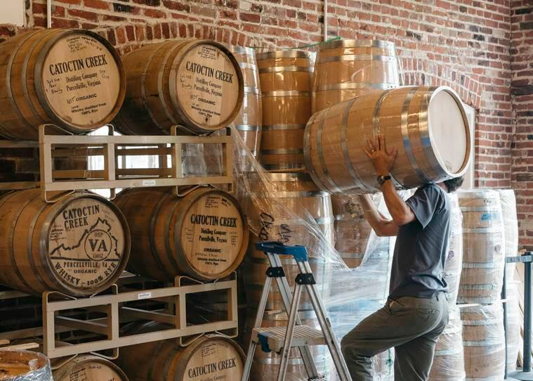 A distiller moves barrels around the warehouse at Catoctin Creek distillery