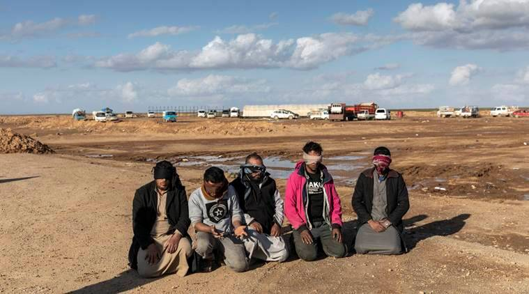 Men who had been arrested by Syrian Democratic Forces soldiers over suspected links to the Islamic State are held in Deir al-Zour province, Syria