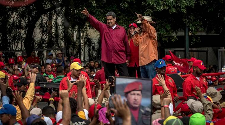President Nicolás Maduro waves to government workers