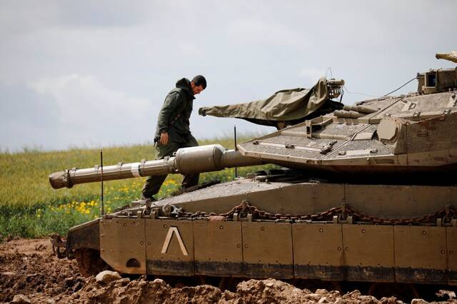 An Israeli soldier stands atop a tank near the border with Gaza, in southern Israel.