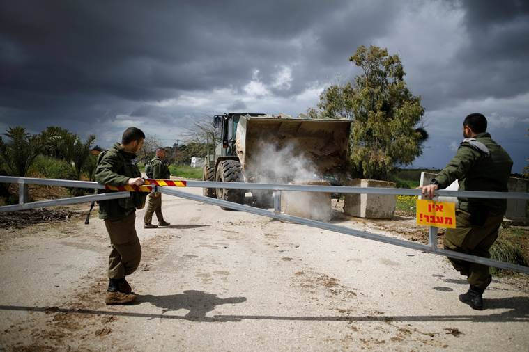 Israeli soldiers watch as a military armoured bulldozer moves concrete barricade blocks