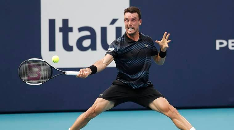 Roberto Bautista Agut of Spain hits a forehand against Novak Djokovic of Serbia (not pictured) in the fourth round of the Miami Open at Miami Open Tennis Complex.