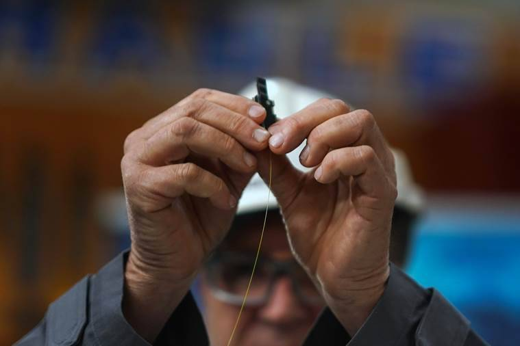 A worker holds a glass strand that will be woven into a fiber-optic cable