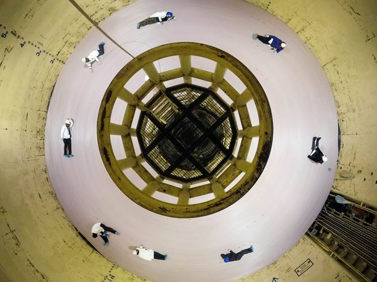 Workers sit on a giant spool of fiber-optic cable
