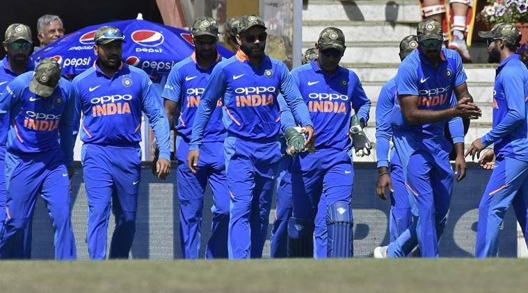 India's captain Virat Kohli (C) and his teammates wearing army camouflage-style caps walk onto the field.