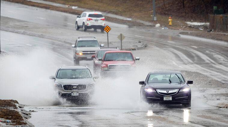 Cars splash through flood water on Ames Avenue west of 66th Street Wednesday