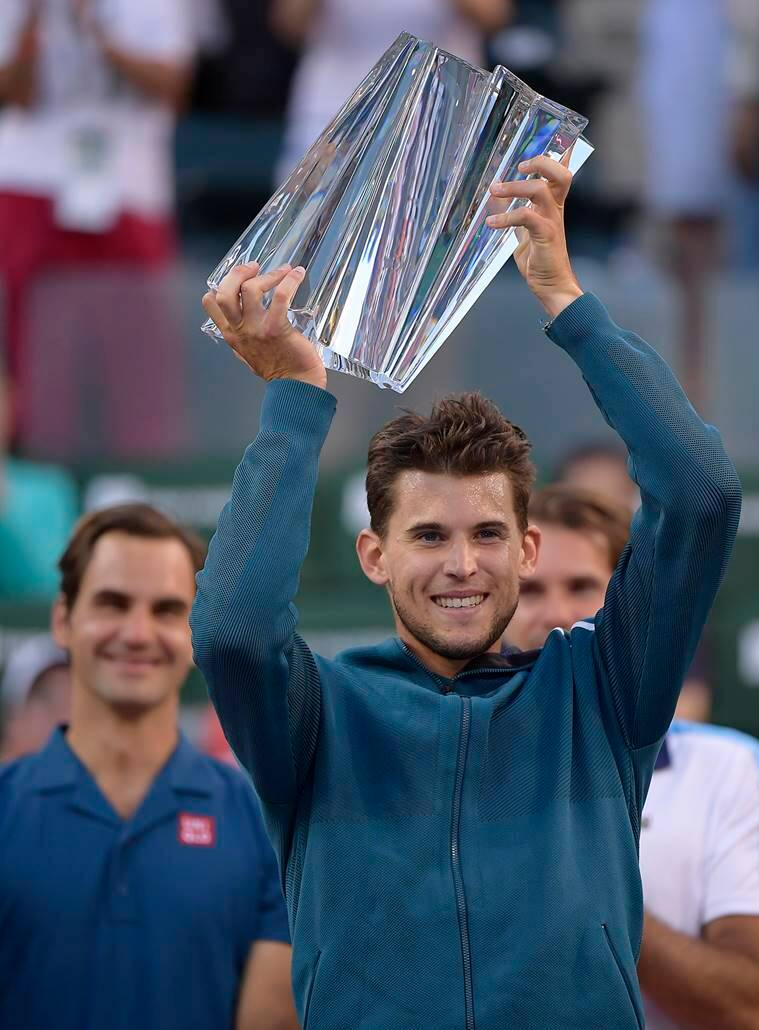 Dominic Thiem, of Austria, foreground, raises a trophy over his head after defeating Roger Federer, of Switzerland, left, in the men's final at the BNP Paribas Open tennis tournament