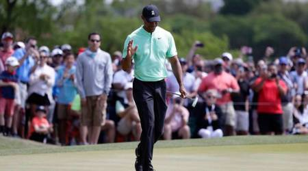 Tiger Woods waves to fans after a putt on the fifth hole during round-robin play at the Dell Match Play Championship golf tournament, Thursday, March 28, 2019, in Austin, Texas