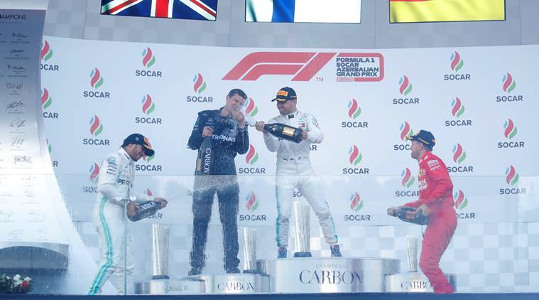 Mercedes' Valtteri Bottas celebrates winning the race with Mercedes mechanic Stuart Green, second placed Lewis Hamilton and third placed Ferrari's Sebastian Vettel on the podium