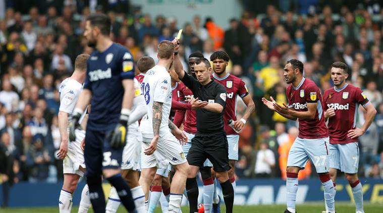 Referee Stuart Attwell shows yellow card during Leeds United vs Aston Villa