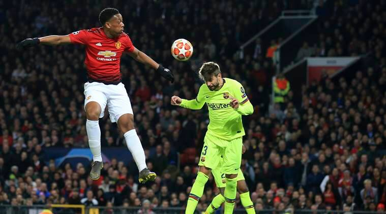 Manchester United's Anthony Martial, left, and Barcelona's Gerard Pique jump for the ball during the Champions League quarterfinal, first leg, soccer match between Manchester United and FC Barcelona at Old Trafford stadium in Manchester, England