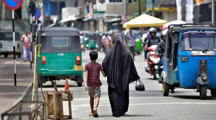 A woman returns from the market with her son in Colombo Monday. (AP)