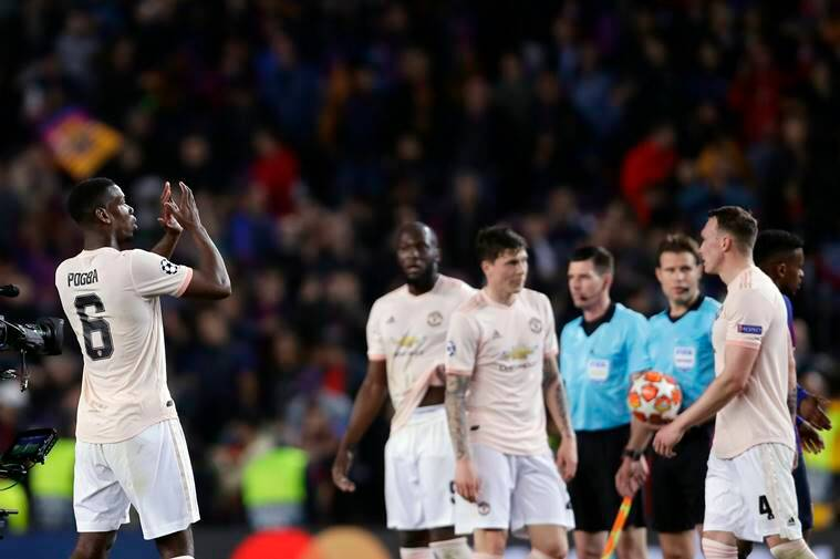 Manchester United's Paul Pogba, left, applauds to supporters at the end of the Champions League quarterfinal, second leg, soccer match between FC Barcelona and Manchester United at the Camp Nou stadium in Barcelona, Spain