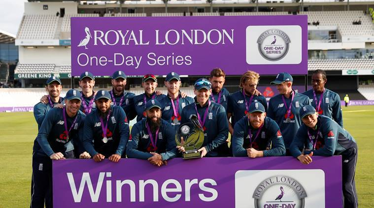 England players pose as they celebrate winning the match with the trophy