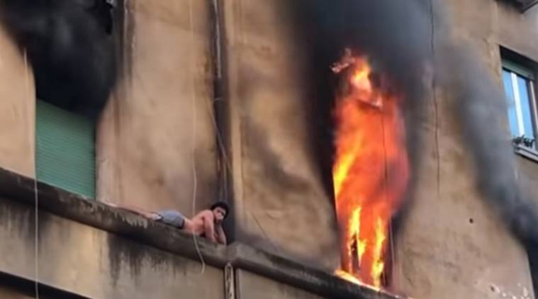 rome, rome fire, man on ledge, man on building ledge, man escapes fire, fire in rome, rome building on fire, viral video, indian express, indian express news
