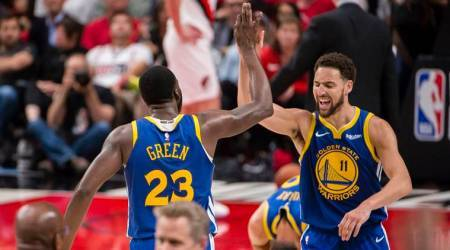 Golden State Warriors guard Klay Thompson (11) celebrates with forward Draymond Green (23) after Green scored a three-point basket in overtime against the Portland Trail Blazers in game four of the Western conference finals of the 2019 NBA Playoffs at Moda Center.