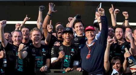 Mercedes team drivers Lewis Hamilton of Britain, right, winner of the race, flanked by his teammate second place Nico Rosberg of Germany and Mercedes non-Executive Chairman former F1 driver Niki Lauda celebrate with all team members after the Formula One Russian Grand Prix at the 'Sochi Autodrom' Formula One circuit, in Sochi