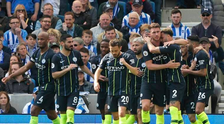 Manchester City's Aymeric Laporte is hugged by teammate Kyle Walker, foreground right, after scoring his side's second goal during the English Premier League soccer match between Brighton and Manchester City at the AMEX Stadium