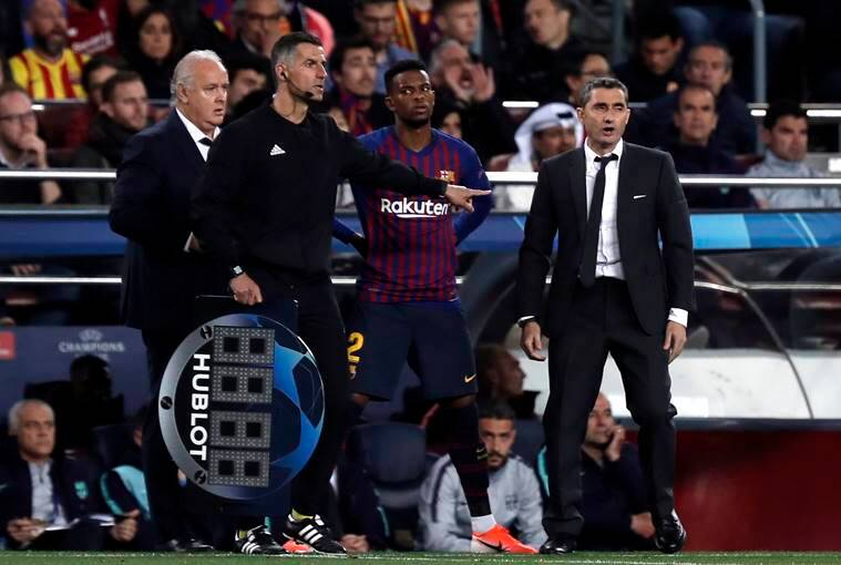 Barcelona's Nelson Semedo, center, stands next to Barcelona coach Ernesto Valverde, right, waiting to enter the pitch during the Champions League semifinal, first leg, soccer match between FC Barcelona and Liverpool at the Camp Nou stadium in Barcelona Spain