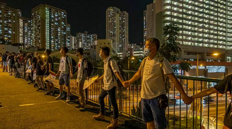Hong Kong protesters, calling for direct elections, join hands across city