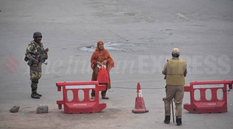 Armed security personnel guard a street in Srinagar where curfew has been imposed by the administration. Express Photo by Shuaib Masoodi