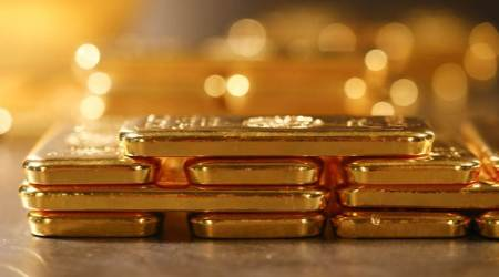 Gold scales 7-year high on rising economic worries, Fed stimulus, SPDR Gold holdings rise to highest since June 2013, global gold price news tuesday, business news india, commodity market news, indian express business news