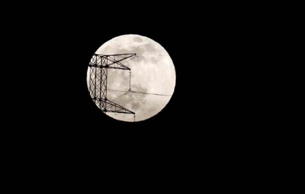 The full moon is seen rising behind an electric tower during the penumbral lunar eclipse in Ronda, near Malaga