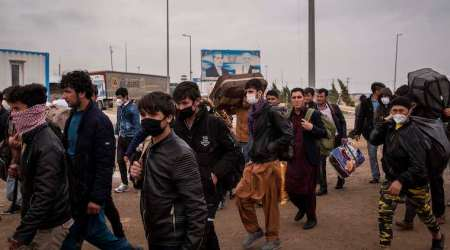 Afghans returning from Iran cross the border into Afghanistan