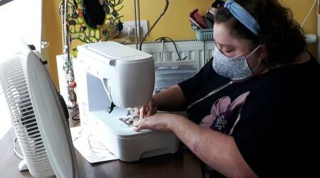 Sien Lagae, works on a mouth mask, meant to help protect from the spread of COVID-19, on her sewing machine at home in Torhout, Belgium.