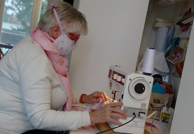 Magda Leonard, sews a face mask, meant to help protect from the spread of COVID-19, at her home in Edegem, Belgium.