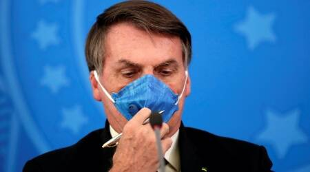 Brazil's President Jair Bolsonaro adjusts his protective face mask at a press statement during the coronavirus disease (COVID-19) outbreak in Brasilia