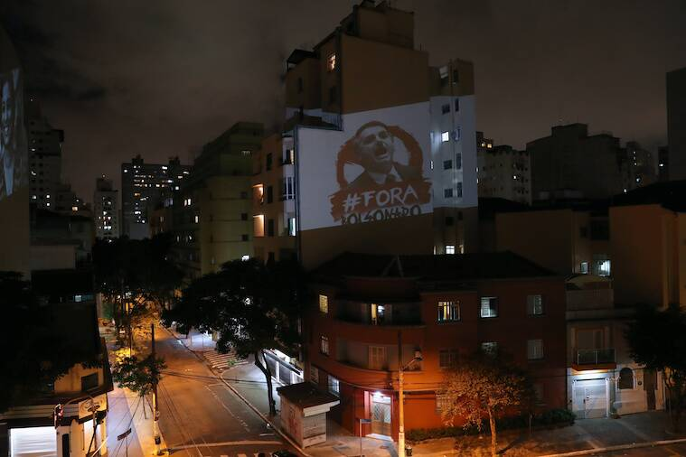 "An image depicting Brazil's President Jair Bolsonaro and the phrase ""out Bolsonaro"" is projected during Bolsonaro's statement on TV about the coronavirus disease (COVID-19) outbreak in Sao Paulo"