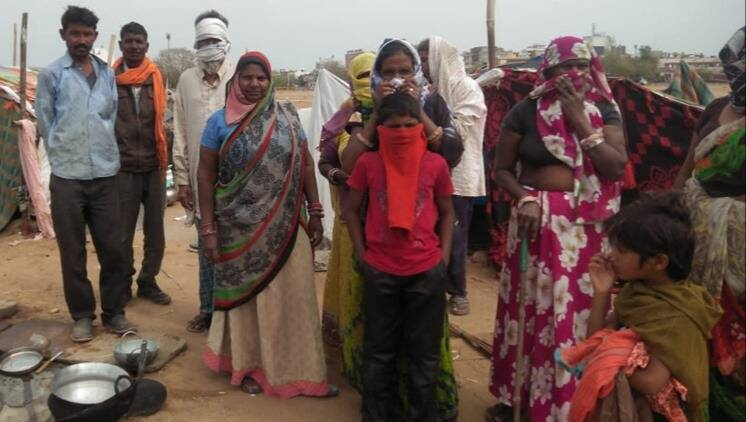 Gujarat: Police bring group of migrant labourers back from road, help them with groceries
