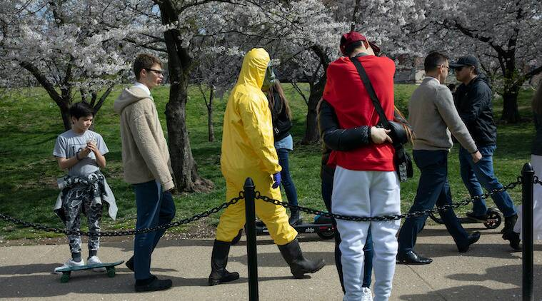 A 17-year-old who asked not to be named wears a yellow hazmat suit, gas mask, boots, and gloves as he walks past a couple in an embrace, as he and his family from Gaithersburg, Md. walk under cherry blossom trees in full bloom on their way to the tidal basin in Washington