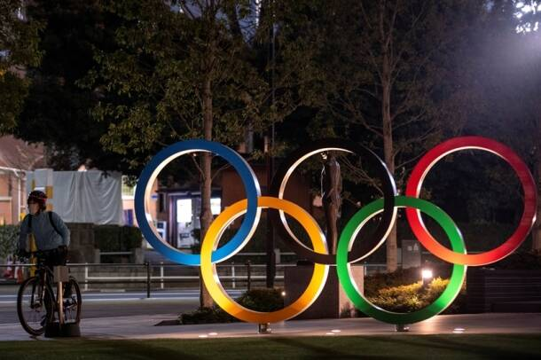 A woman wearing a protective face mask, following the outbreak of the coronavirus, rides her bicycle past The Olympic rings in front of the Japan Olympics Museum in Tokyo