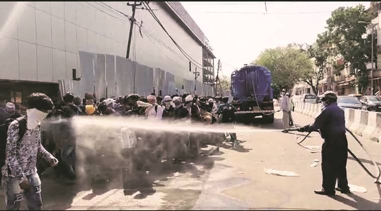 delhi lockdown, delhi migrant labourers, delhi coronavirus, delhi migrants sprayed with disinfectant, delhi city news, Lajpat Nagar migrants sprayed with disinfectant