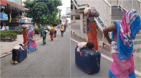 migrnats on road, kid falls asleep on suitcase, mother drags asleep baby on trolley, viral videos, migrant workers crisis, covid-19 lockdown india, indian express