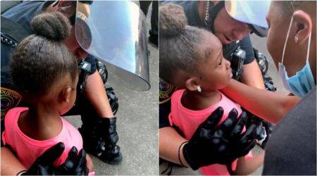 police officer comforts girl protest, black girl comforted by cops, houston police comfort girl protest rally, black lives matter, blm protest, george floyd, viral videos, indian express