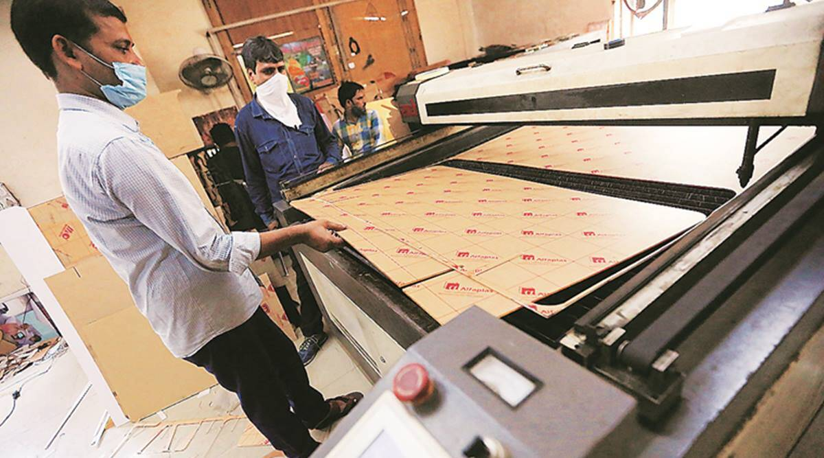 A workshop in a lane cuts glass to stand between Delhi power corridors, virus