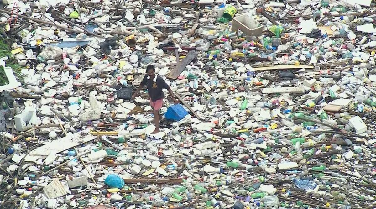 brazil, Rio Sarapuí, Rio Sarapuí pollution, Sarapui River pollution, man walks on polluted river, man walks on garbage in river, viral video, indian express