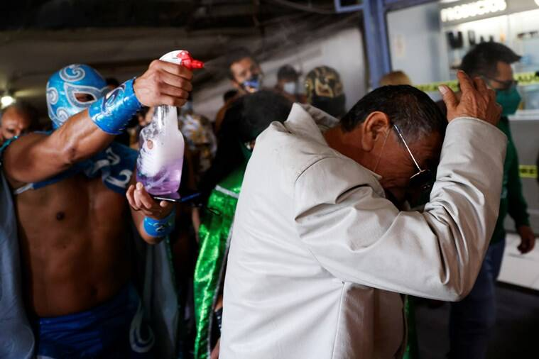 mexico wrestlers put mask on people, covid 19 facemask, wrestlers force facemask on mexico market, lucha libre wrestlers mask campaign, viral news, indian express news