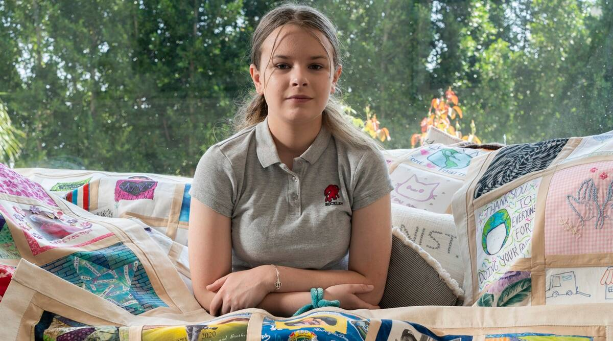 Madeleine Fugate, 14, who has created a COVID-19 Memorial Quilt Ñ inspired by the AIDS Memorial Quilt of the 1980s Ñ of fabric squares donated by people who lost loved ones to the virus, at her home in Los Angeles, Calif., July 17, 2021. (Gabriella Angotti-Jones/The New York Times)