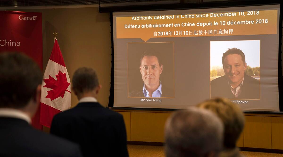 A video screen displays images of Canadians Michael Kovrig, left, and Michael Spavor at an event held in connection with the announcement of the sentence for Spavor at the Canadian Embassy in Beijing.